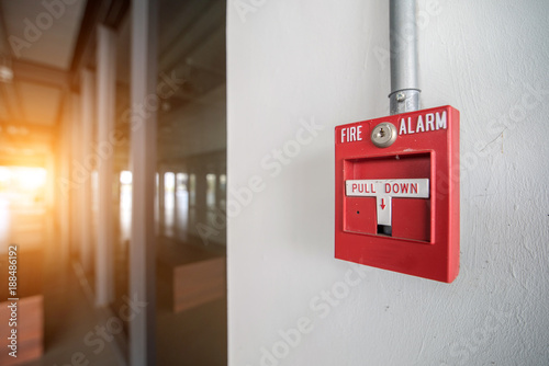 Photo Red fire alarm mounted on the crack wall