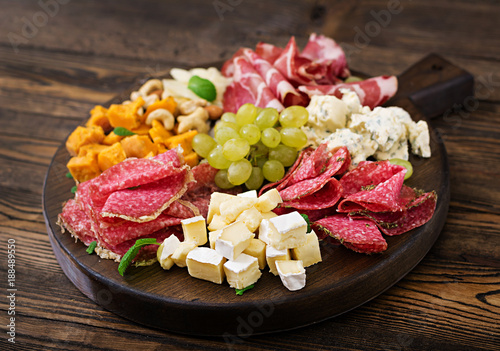 Poster Entree Antipasto catering platter with bacon, jerky, sausage, blue cheese and grapes on a wooden background.
