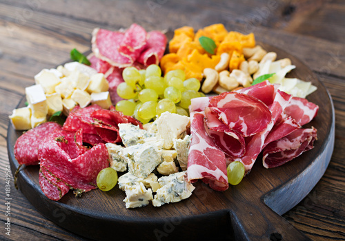 Recess Fitting Appetizer Antipasto catering platter with bacon, jerky, sausage, blue cheese and grapes on a wooden background.