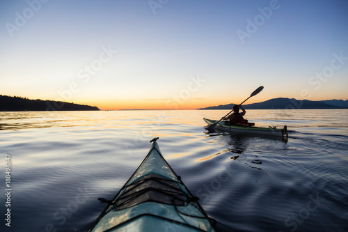 Fotomural  Adventure Woman Kayaking on a Sea Kayak during a Vibrant Sunset