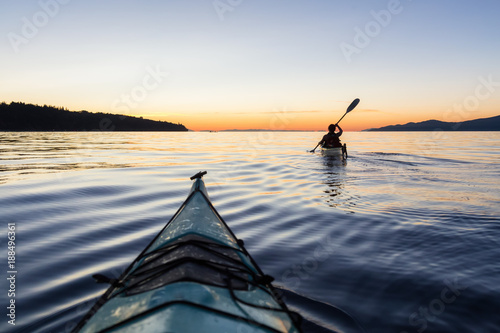 Adventure Woman Kayaking on a Sea Kayak during a Vibrant Sunset Wallpaper Mural
