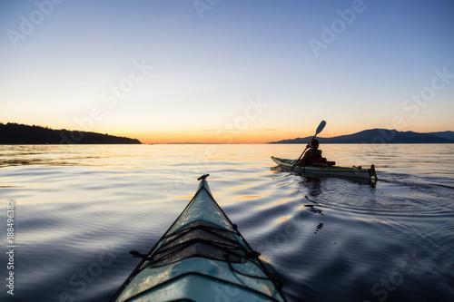 Fotografie, Obraz  Adventure Woman Kayaking on a Sea Kayak during a Vibrant Sunset