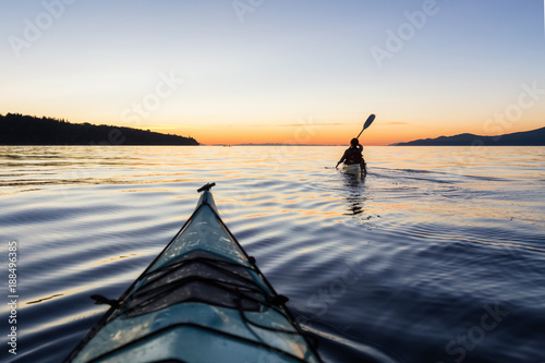 Valokuva  Adventure Woman Kayaking on a Sea Kayak during a Vibrant Sunset