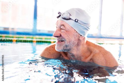 Slika na platnu Senior man in an indoor swimming pool.