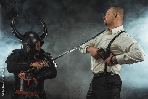 Fotografia, Obraz  armored samurai with katana ready to kill man while he taking out his gun