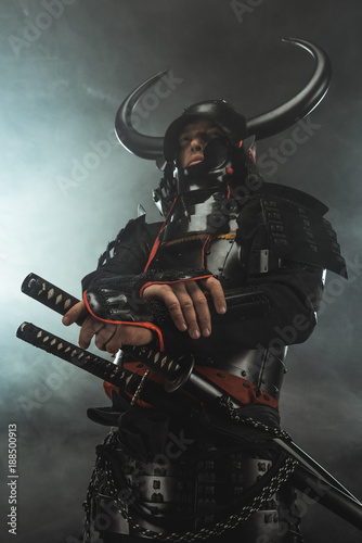 bottom view of samurai in traditional armor with swords on dark background with Wallpaper Mural