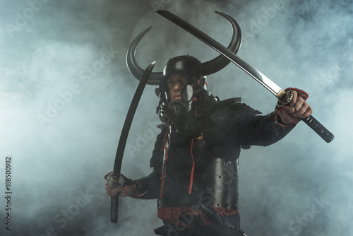 Photo samurai in traditional armor with dual katana swords in defence position on dark