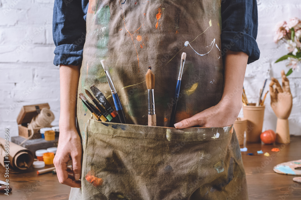 Fototapeta cropped image of artist with brushes and hand in apron pocket