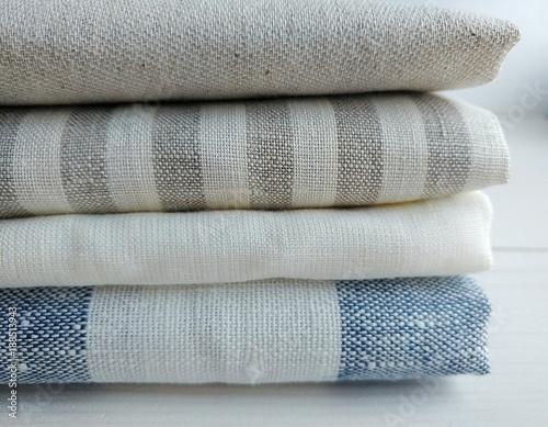 Obraz na plátně Pile of striped white grey blue red linen cotton fabrics on white background