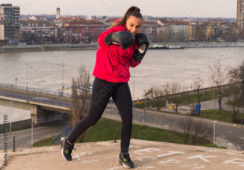 Garden Poster Martial arts Young girl wearing boxing gloves throwing a punch - martial arts training