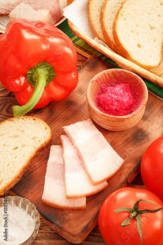 Breakfast with jowl pork bacon, red horseradish sauce, bread, pepper and tomatoe Fototapeta