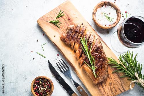 Staande foto Vlees Grilled beef striploin steak with red wine glass.