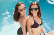 happy young women in bikini and swimsuit at poolside looking at camera