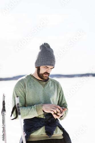 Fotobehang Wintersporten Bearded man looking at object in hands in winter