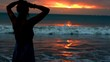 Silhouette of the woman standing next to the seaside during sunset, steadycam sh