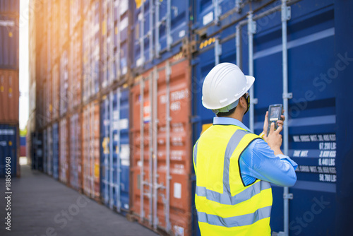Fotografia, Obraz  Foreman control loading Containers box from Cargo freight ship for import export