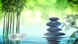 Zen stones and two burning candles on the calm surface of the water and a bamboo grove in the distance