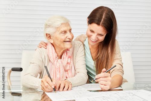 Fotografia  Mädchen und Seniorin lösen Rätsel zusammen