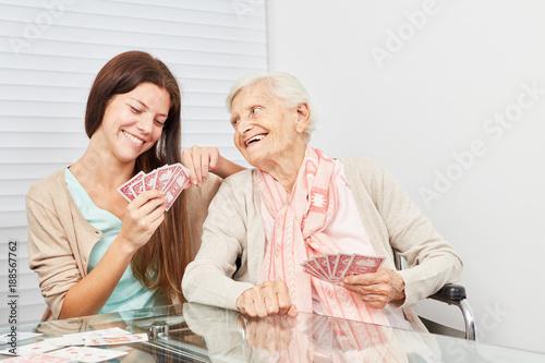 фотография  Junge Frau und Seniorin beim Karten spielen