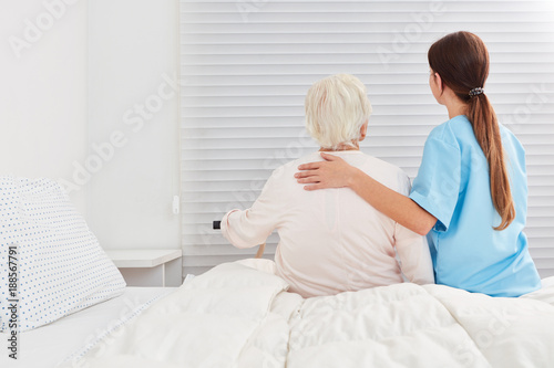 Obraz Pflegerin hilft Seniorin aus dem Bett in der Reha - fototapety do salonu