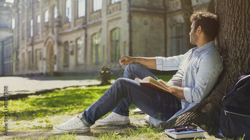 Fotografía  Multinational guy sitting under tree with book, looking sideways, leisure time