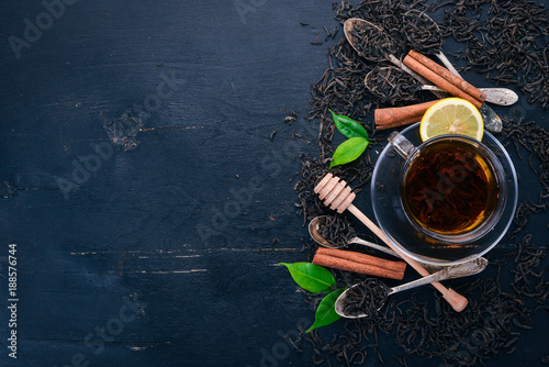 Staande foto Thee Tea in a glass cup with spices and herbs. On a black wooden background. Top view. Copy space.