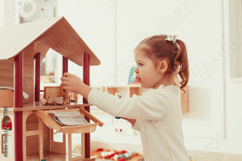 Girl playing with a dollhouse Canvas-taulu