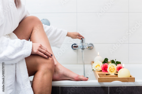 Fotografie, Obraz  Woman preparing wellness bath with flowers, candles and fragrance oil in tub