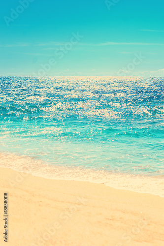 Staande foto Strand Summer beach and soft wave background. Sand and sea. Tropical summer vacation image in vintage hipster style color tone.