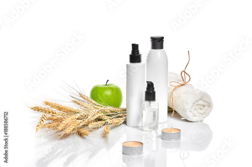 Poster Spa Spa cosmetics, jar of cream, oil with wheat, white cosmetic bottles with apple and wheat towel, candle, soap isolated on white. Without label.