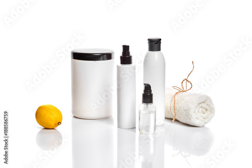 Keuken foto achterwand Spa White bottles and one whole lemon isolated on white background. The concept for advertising cosmetics