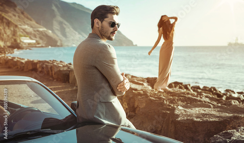 Tuinposter Artist KB Elegant couple relaxing by the sea