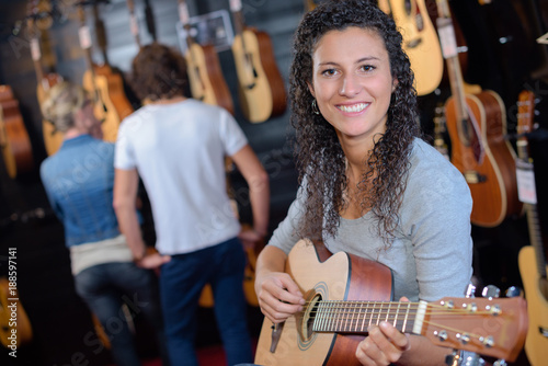 Fotografie, Obraz  woman holding a guitar in the guitar store