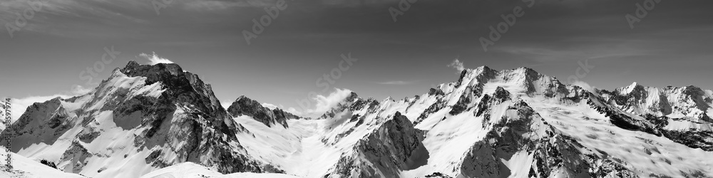 Fototapeta Black and white panoramic view of snow-capped mountain peaks