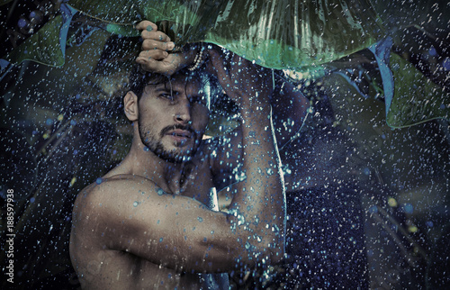 Tuinposter Artist KB Handsome man staring at the tropical raing