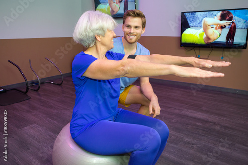 personal trainer coaching senior woman sitting on fitness ball kaufen sie dieses foto und. Black Bedroom Furniture Sets. Home Design Ideas