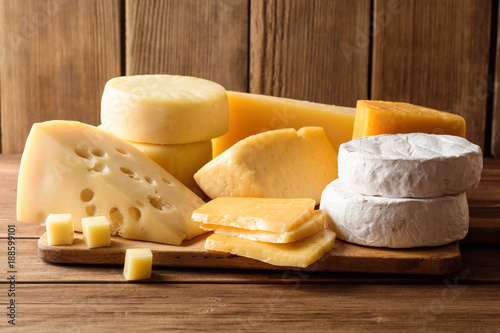 Various types of cheese on dark rustic wooden background.