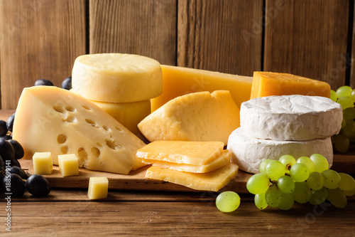 Poster Dairy products Various types of cheese on dark rustic wooden background.