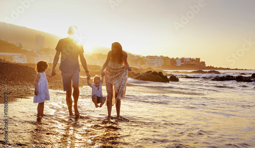 Tuinposter Artist KB Cheerful family having fun on a beach, summer portrait