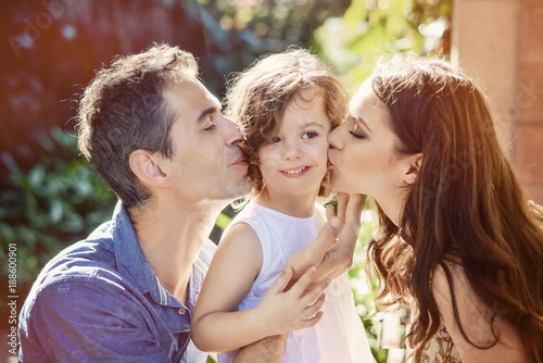 Happy parents kissing their beloved child