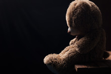 A Lone Teddy Bear Sitting In The Dark, Side View,