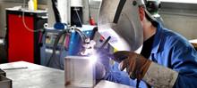 Schweißer Im Stahlbau Einer Firma Arbeitet Mit Einem WIG Schweißgerät // Welder In The Steel Construction Of A Company Works With A TIG Welding Machine