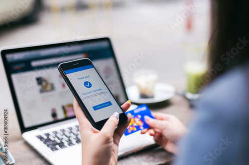 Fotografía  Young asian woman making payment success on mobile smartphone screen and using c