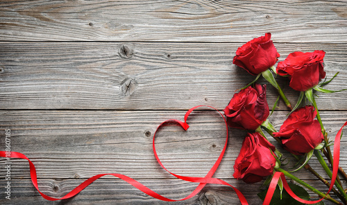 Leinwand Poster Romantic floral frame with red roses and ribbon on wooden background