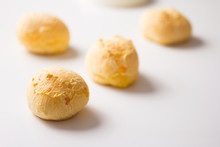 Pao De Queijo Is A Cheese Bread Ball From Brazil. Also Known As Chipa, Pandebono And Pan De Yuca. Snacks Spread Over White Table. Minimalism And Selective Focus.
