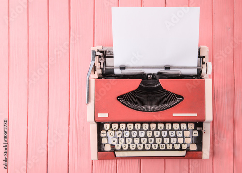 Fotografía  A typewriter on a pink table (top view)