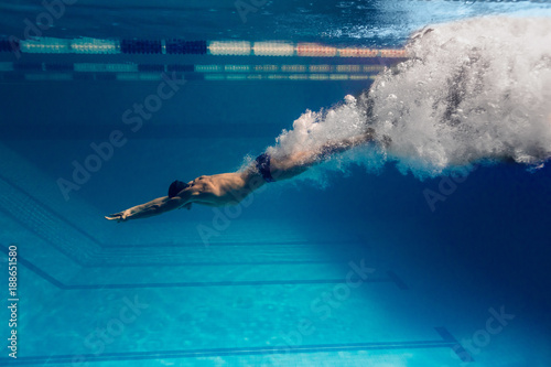 Fotomural underwater picture of male swimmer swimming i swimming pool