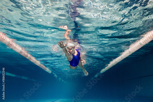 Fotografía  underwater picture of female swimmer in swimming suit and goggles training in sw
