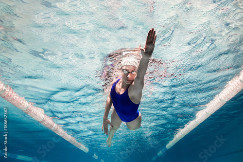 Photo underwater picture of female swimmer in swimming suit and goggles training in sw