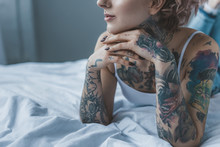 Cropped View Of Dreamy Tattooed Girl Lying On Bed